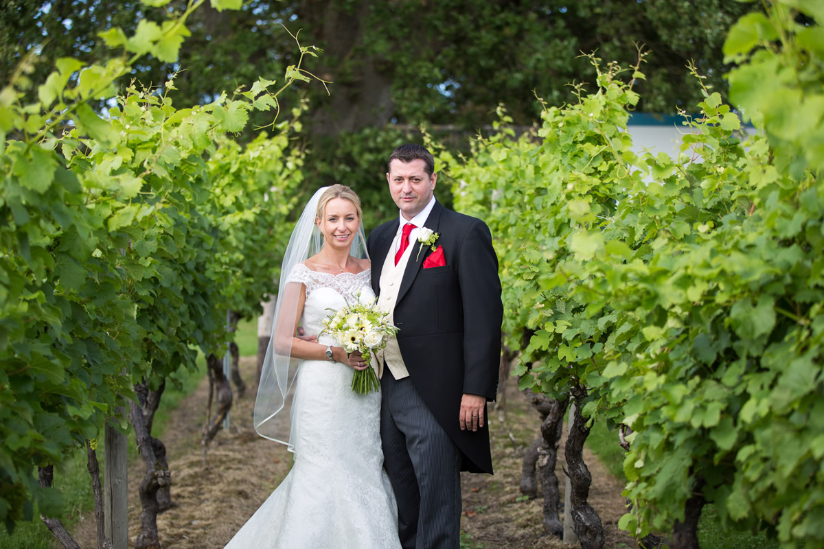 bride and groom in grape vines at chapel down winery