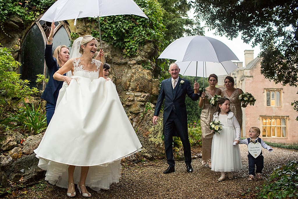 bride lifting her dress up in the rain under an umbrella