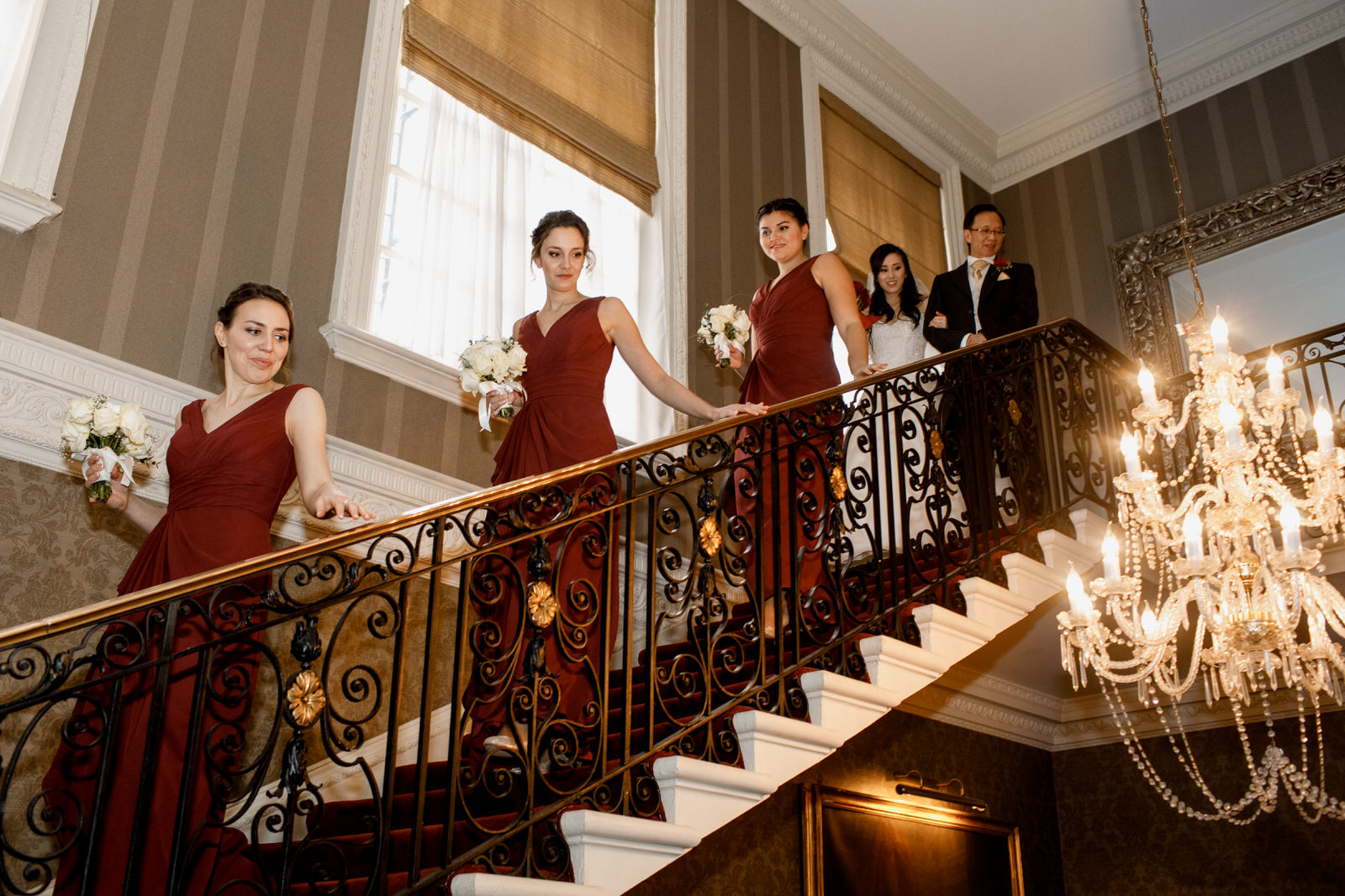 bridesmaids walking down staircase at hedsor house wedding