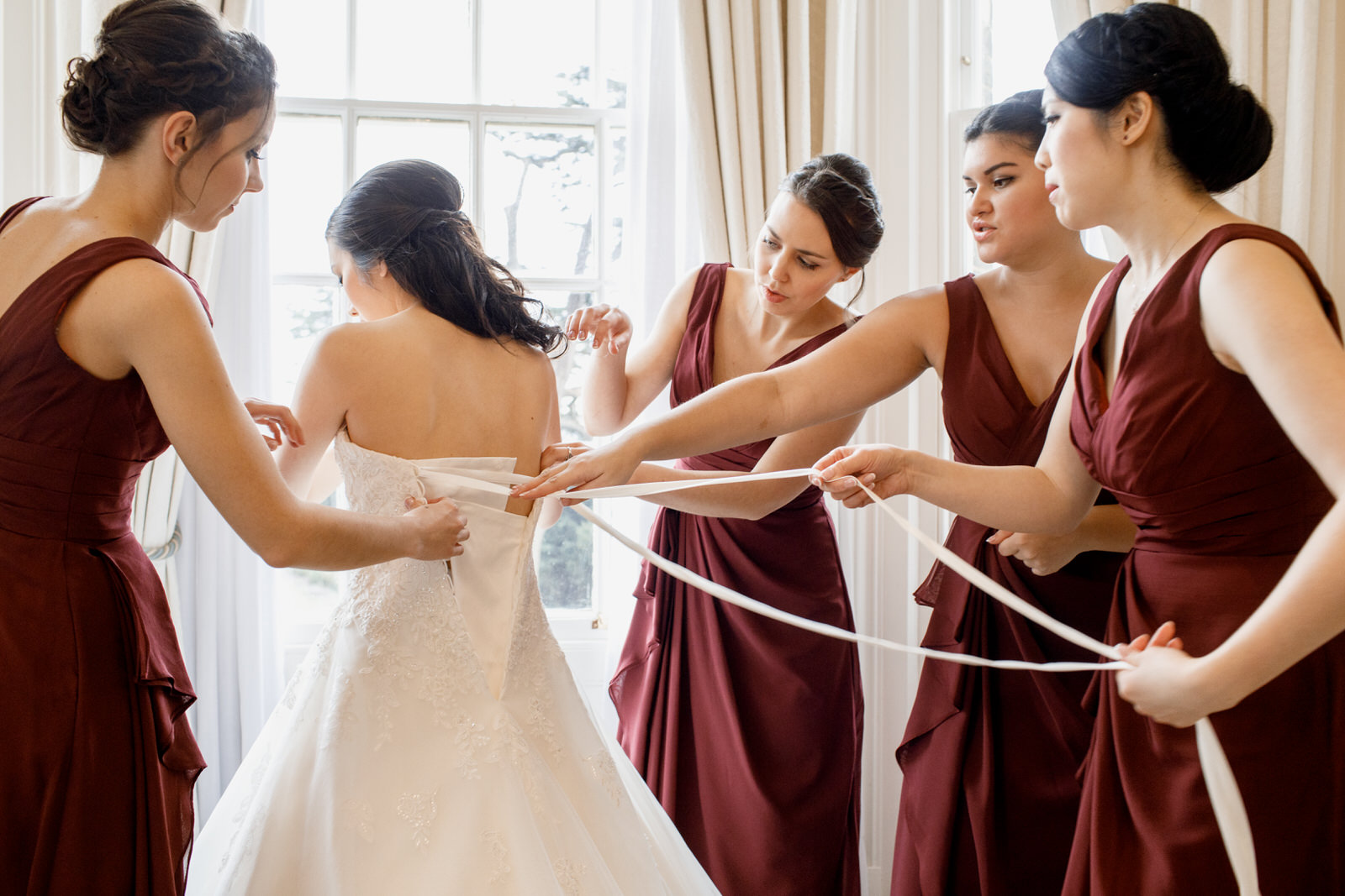 bridesmaids putting on brides dress at hedsor house wedding