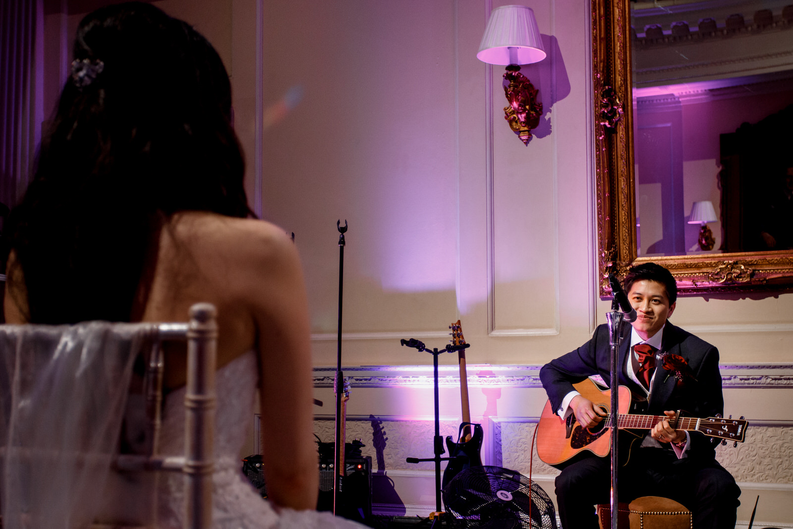 groom playing guitar and singing to bride