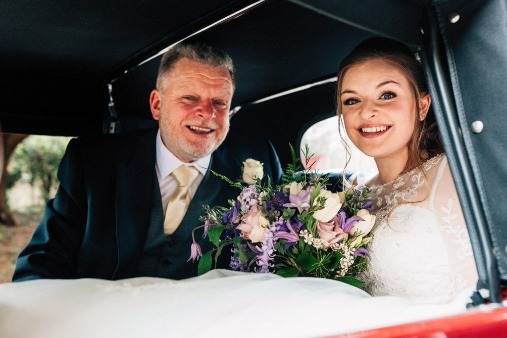 father of the bride with bride in car