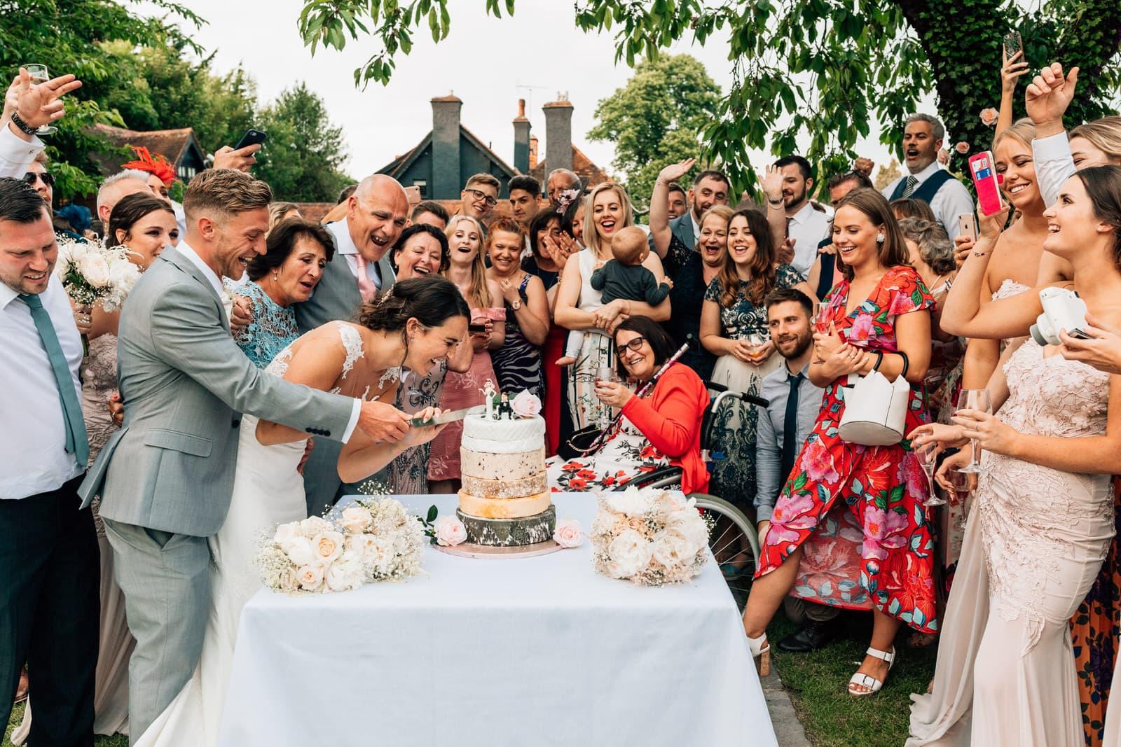 bride and groom cutting cake in garden wedding