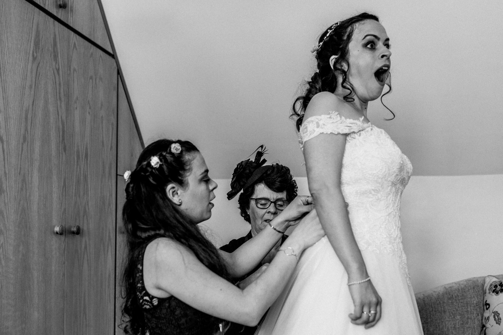bride getting into dress with shocked face
