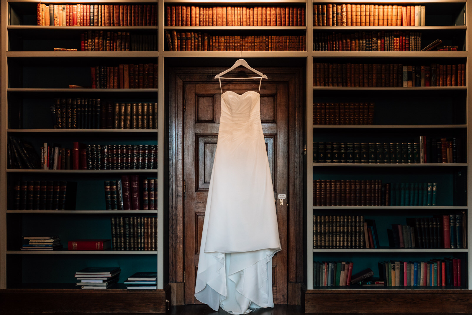 wedding dress hanging against book case