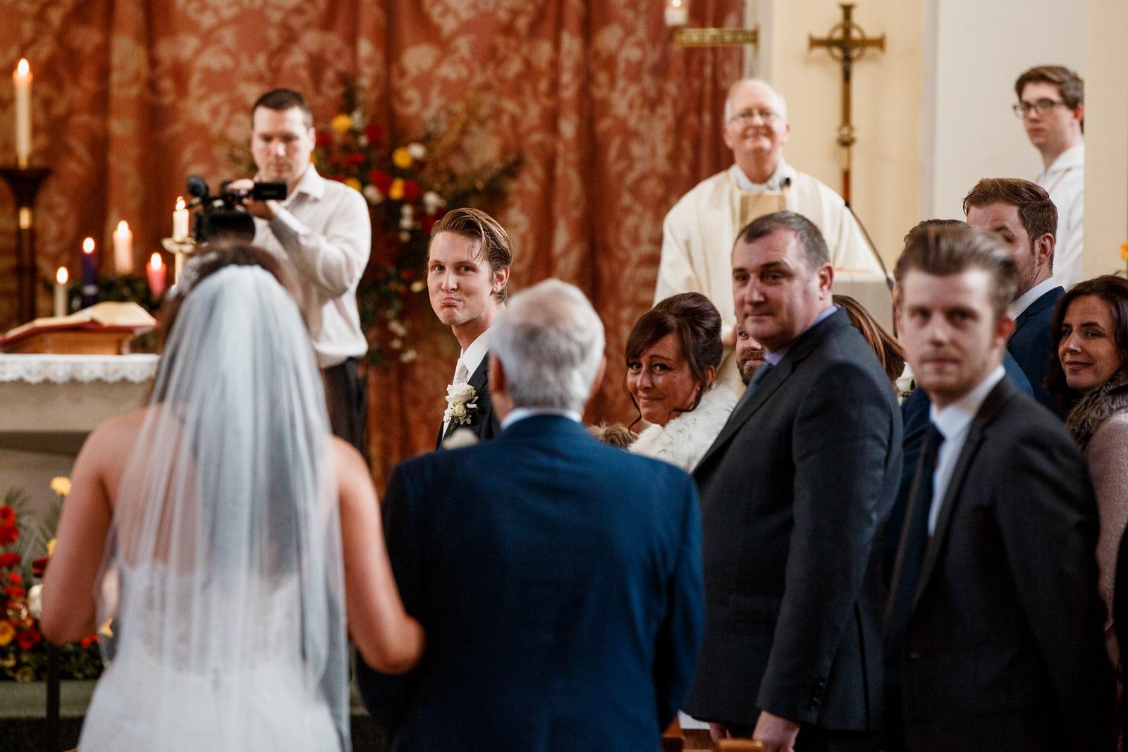 groom looking over shoulder down aisle at bride