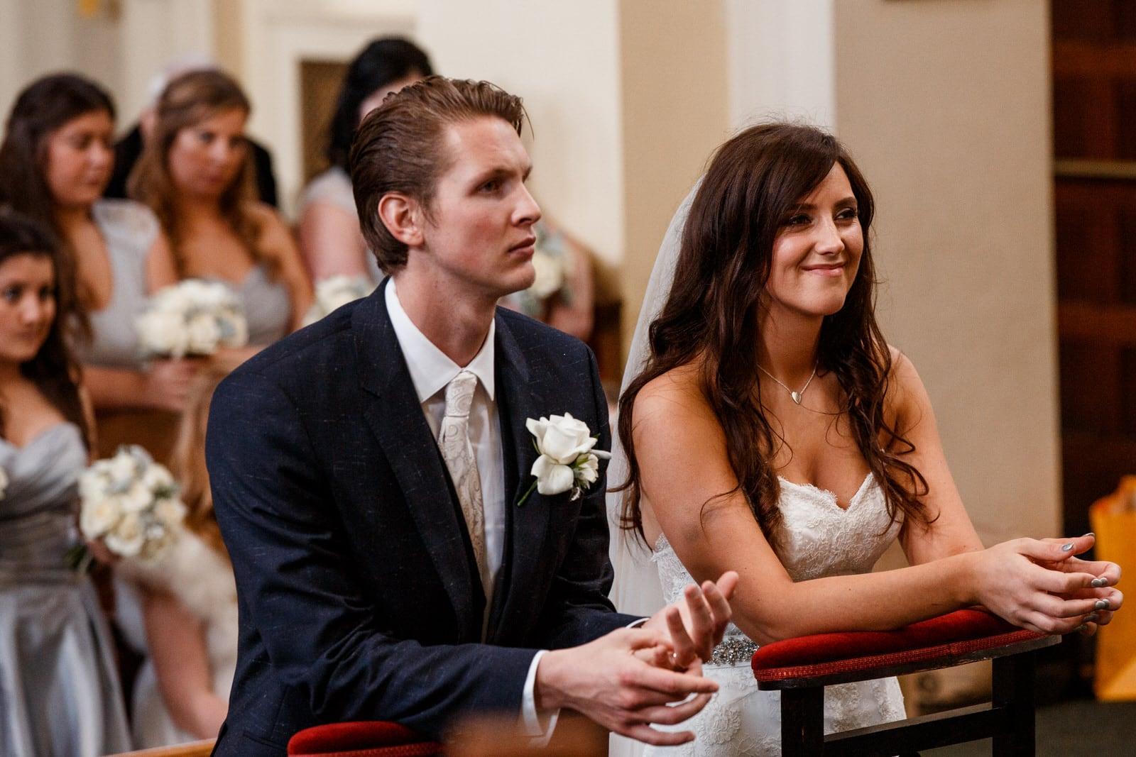 bride and groom kneeling at altar for wedding