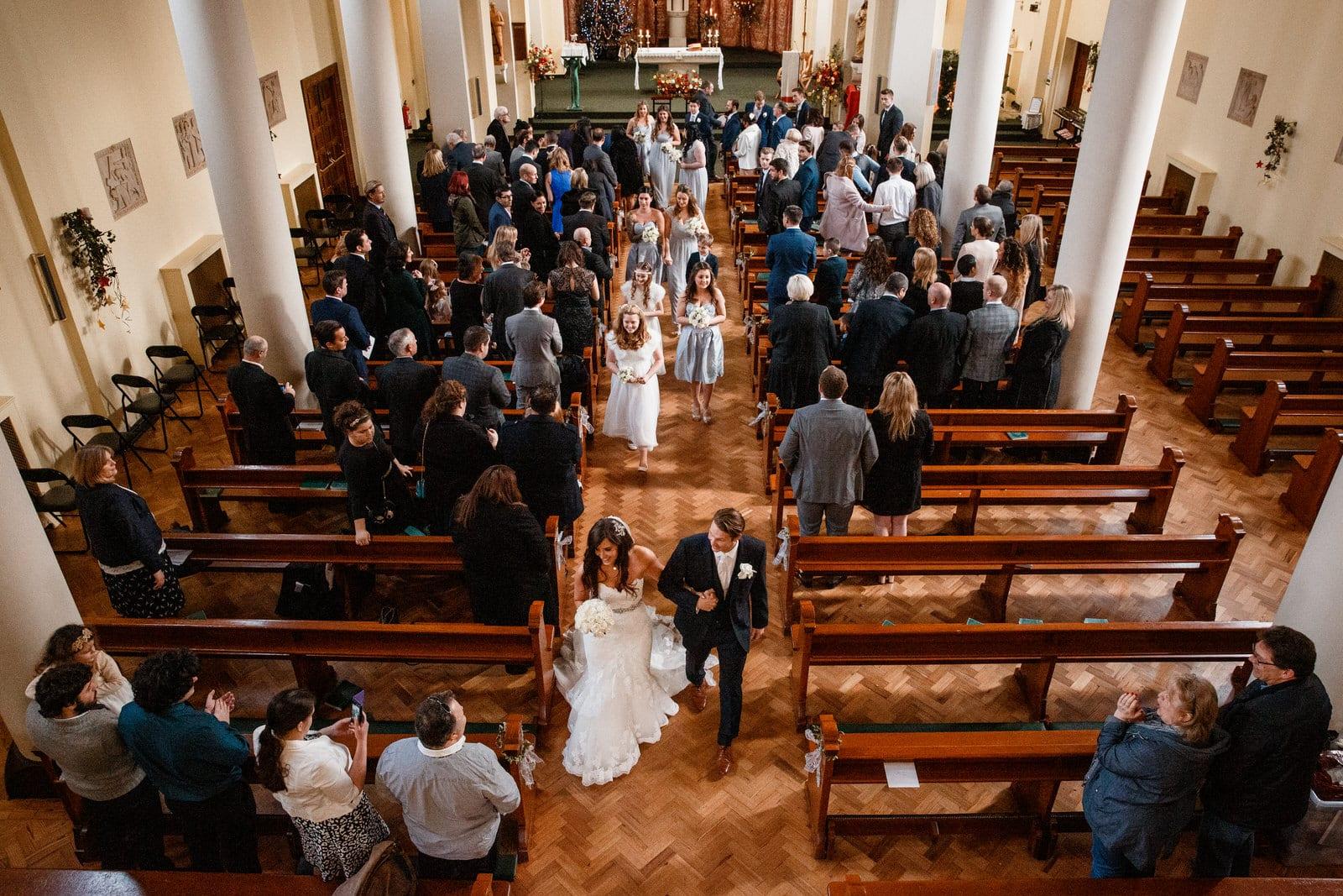 aerial shot of bride and groom leaving church wedding