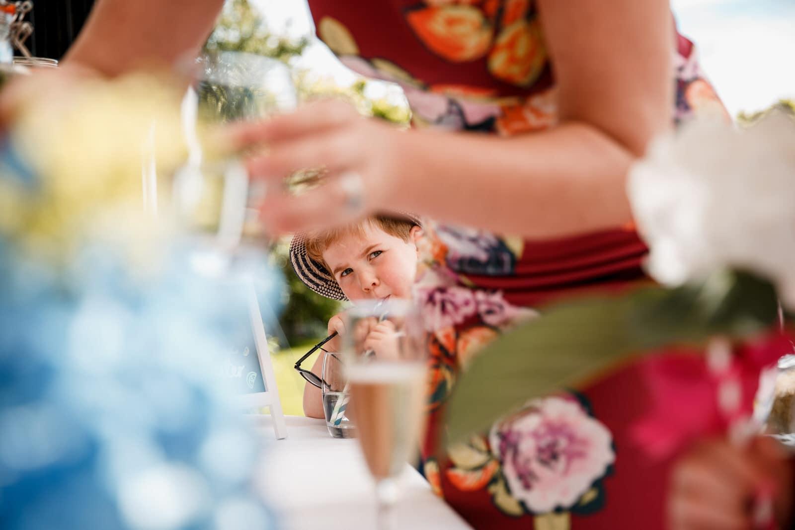 drinks reception and boy looking at mum at lillibrooke manor wedding