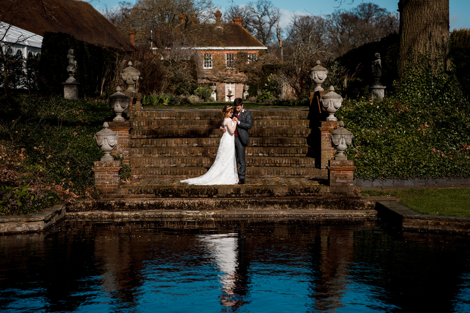 bride and groom standing near steps above a pond