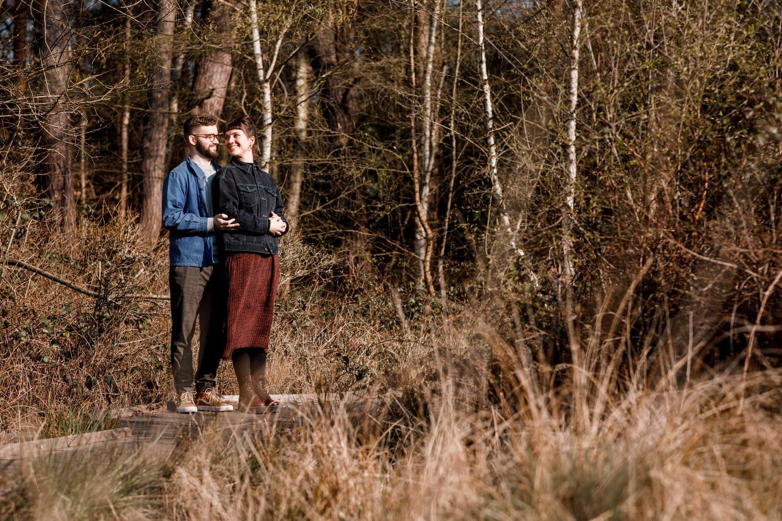 couple standing on wooden walkway at burnham beeches