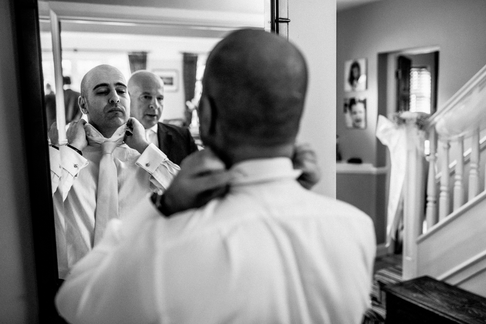 guy putting tie on in mirror for wedding