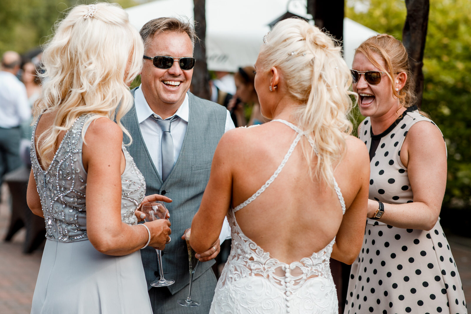 guests laughing at wedding in sunshine
