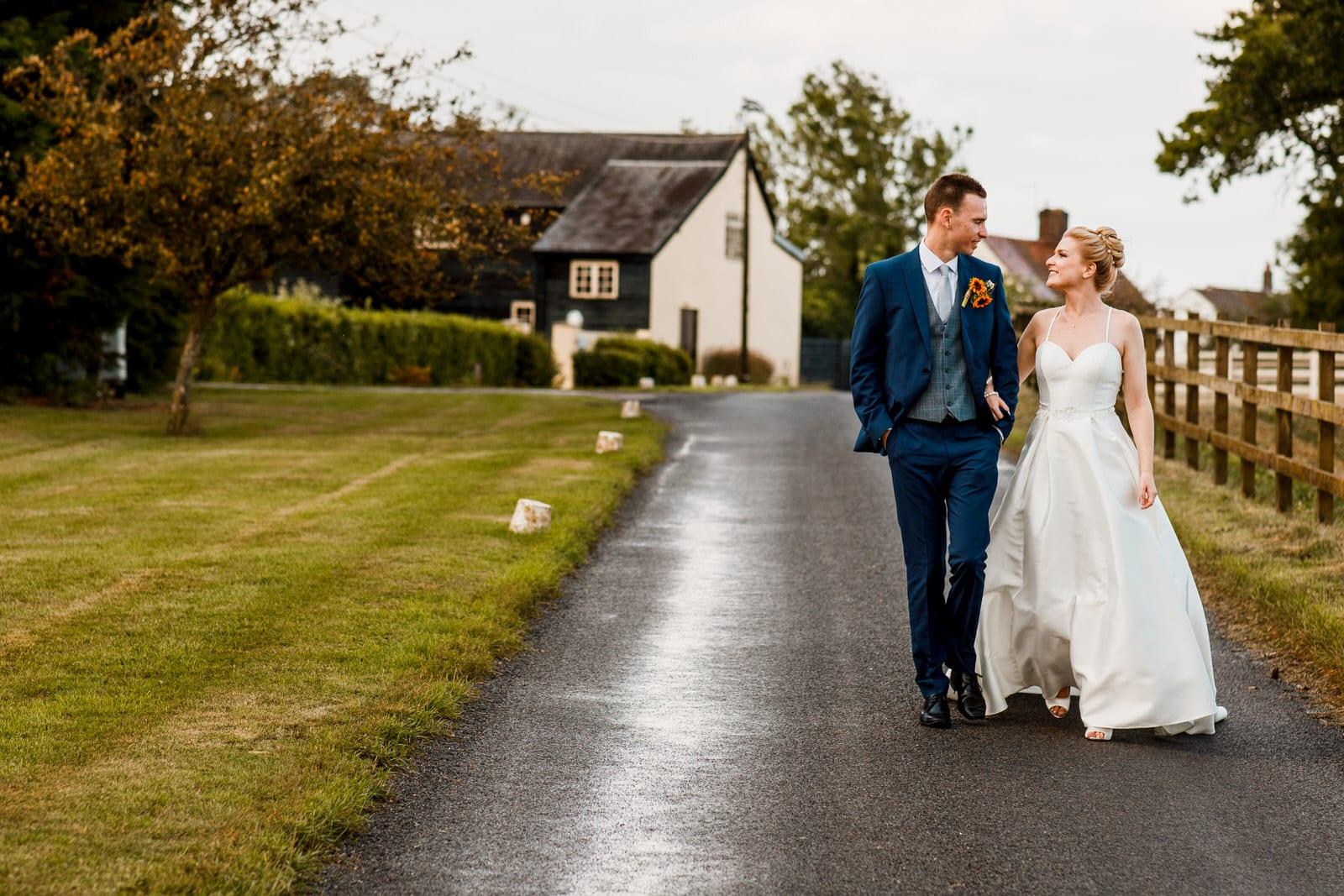 bride ad groom walking outside milling barn