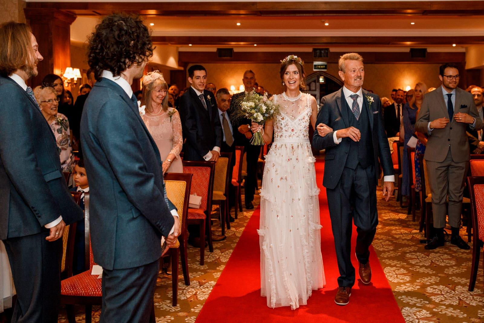 bride walking down aisle at ashdown park hotel