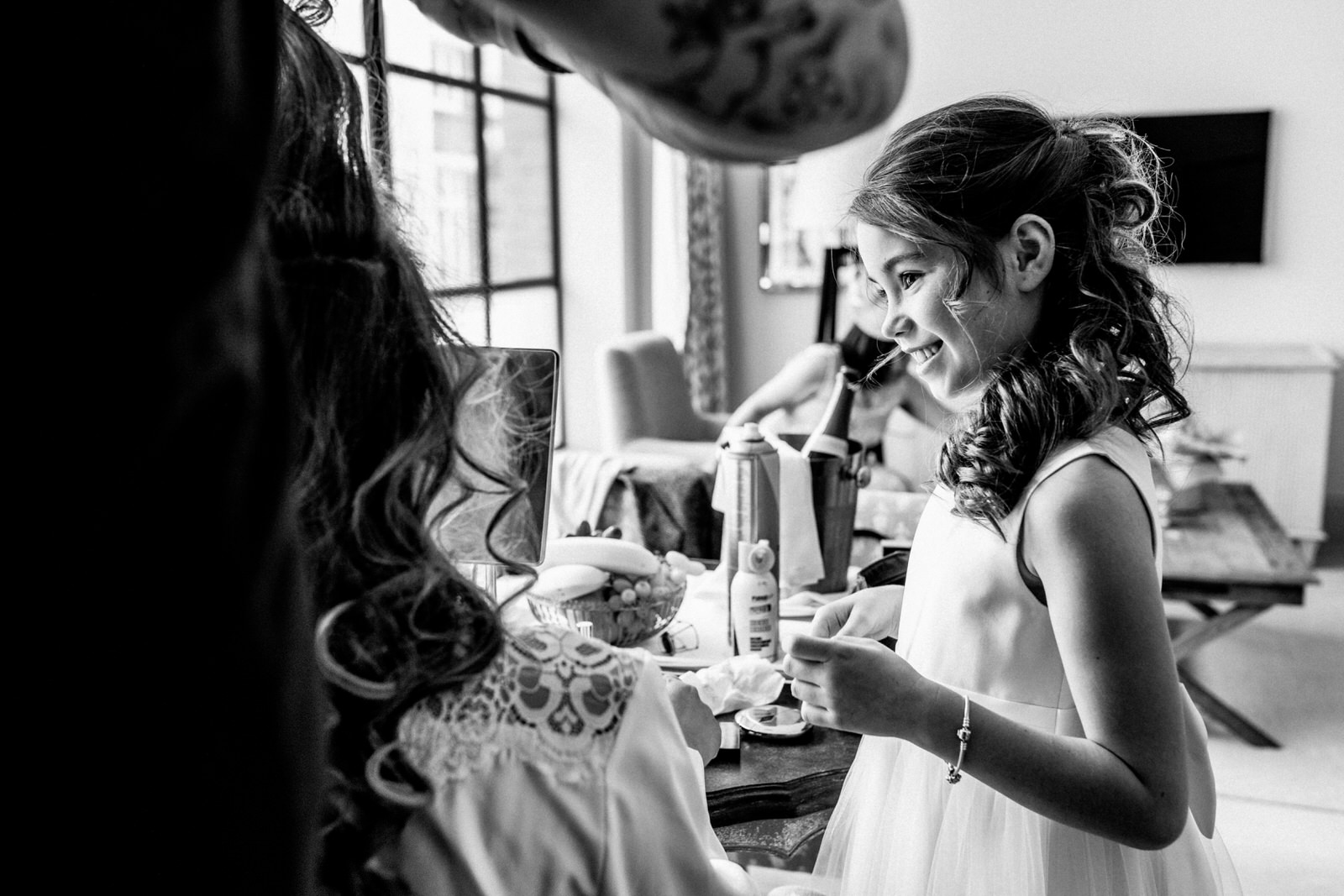 daughter looking at mother whilst she prepares makeup for wedding
