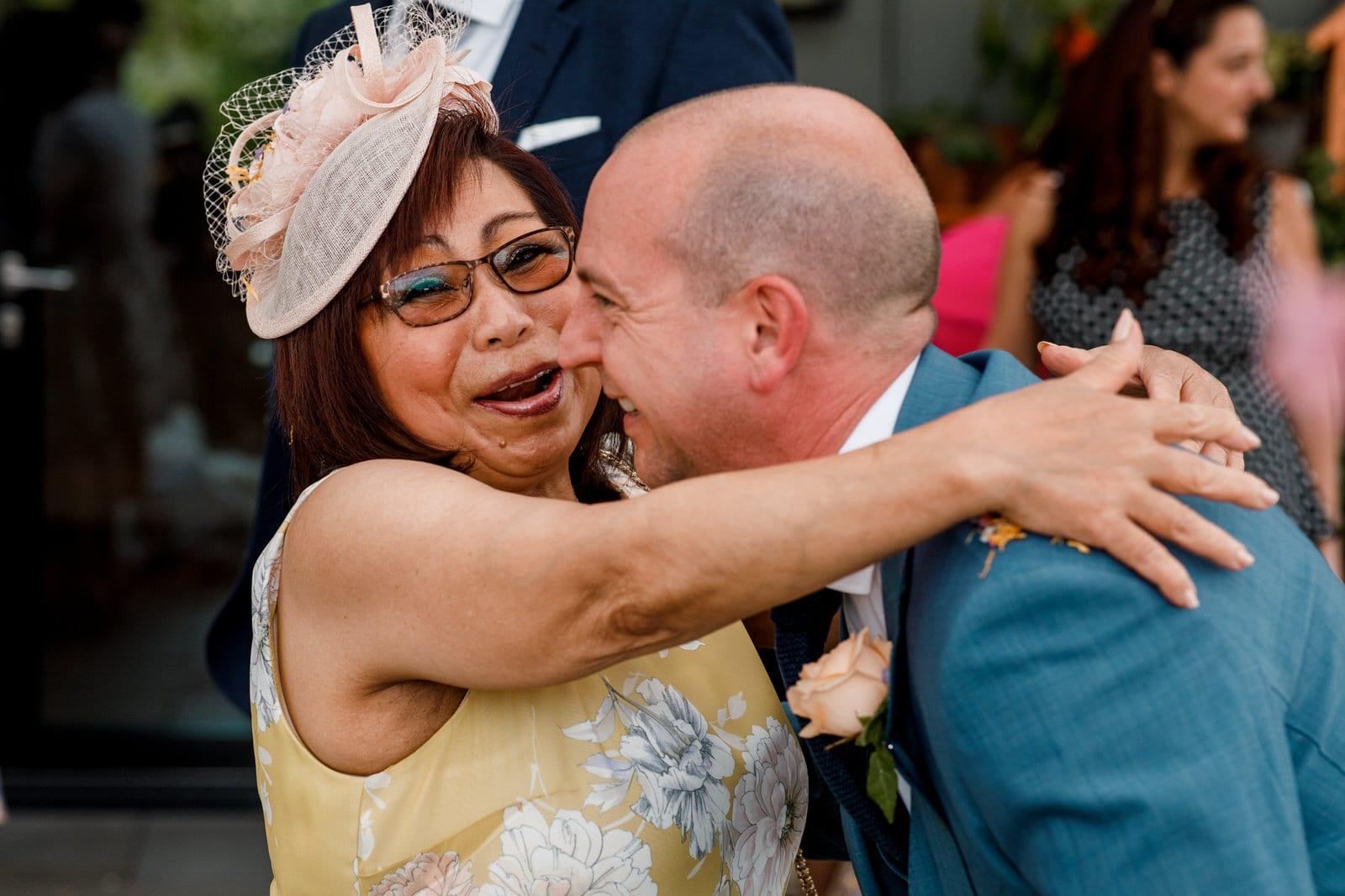 mother of the bride hugging groom