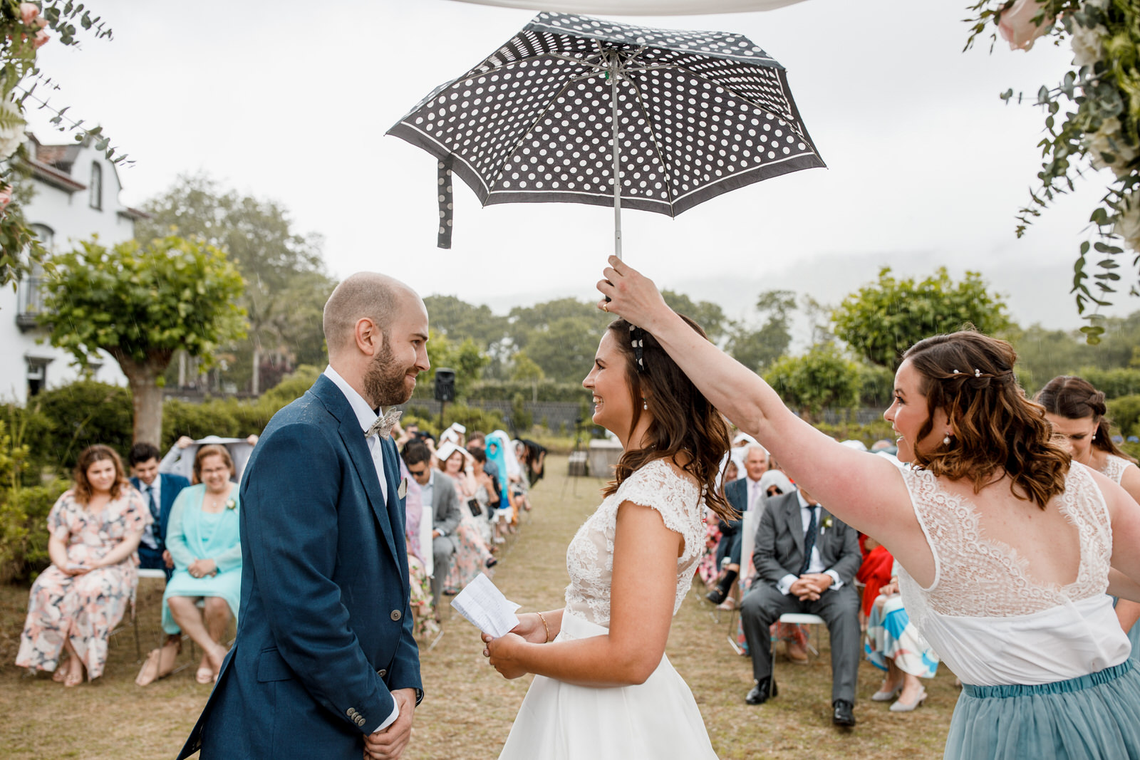 bride and groom standing in rain at destination wedding