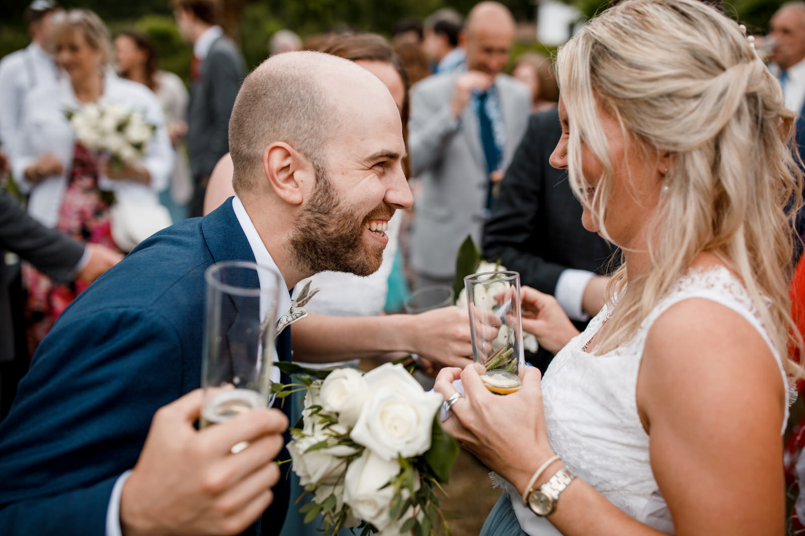 groom laughing with bridesmaid