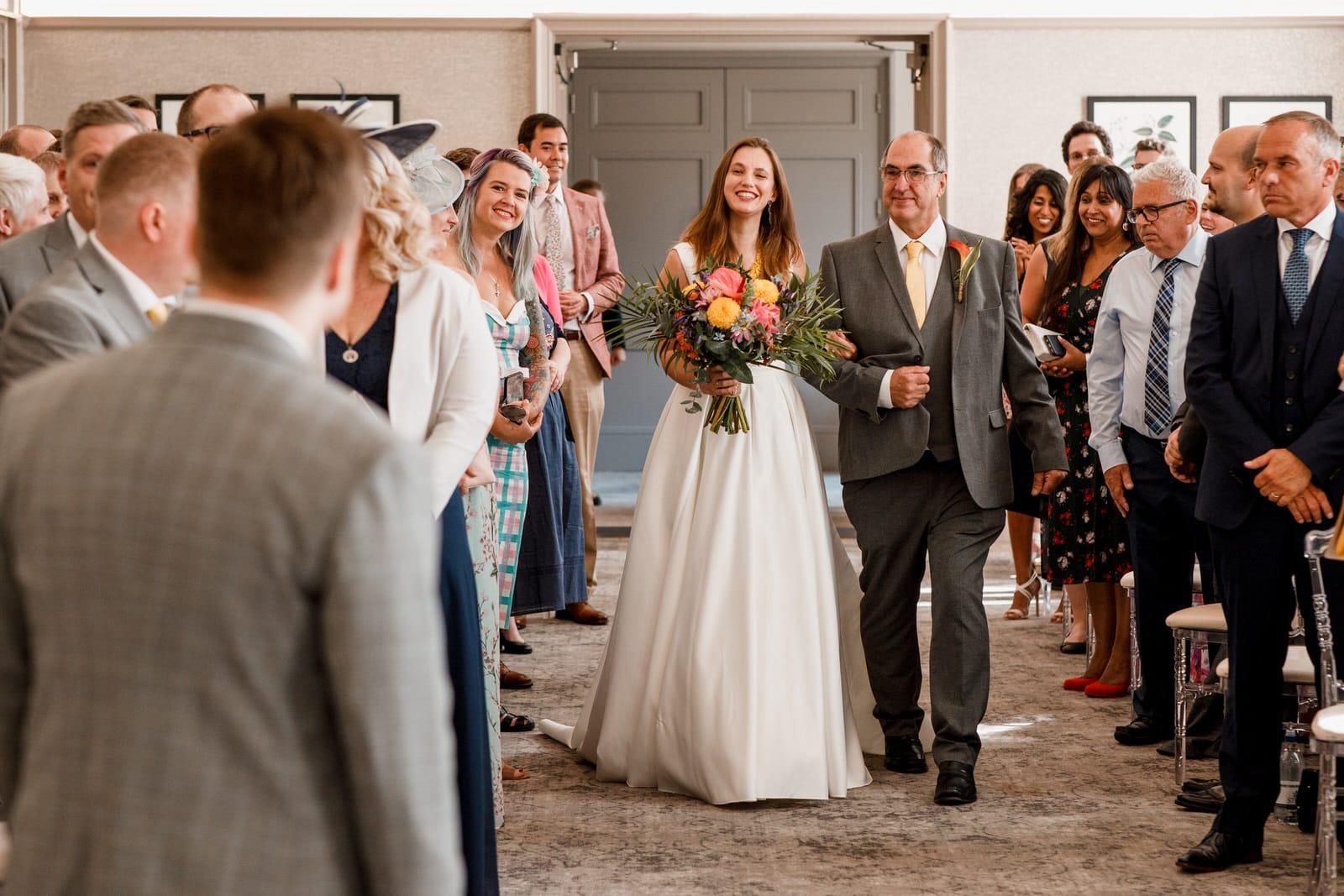 bride waling down aisle at de vere beaumont estate wedding
