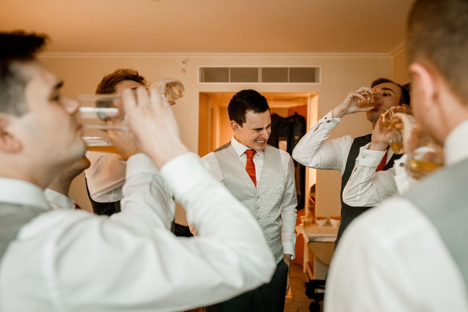 groom having shots with ushers