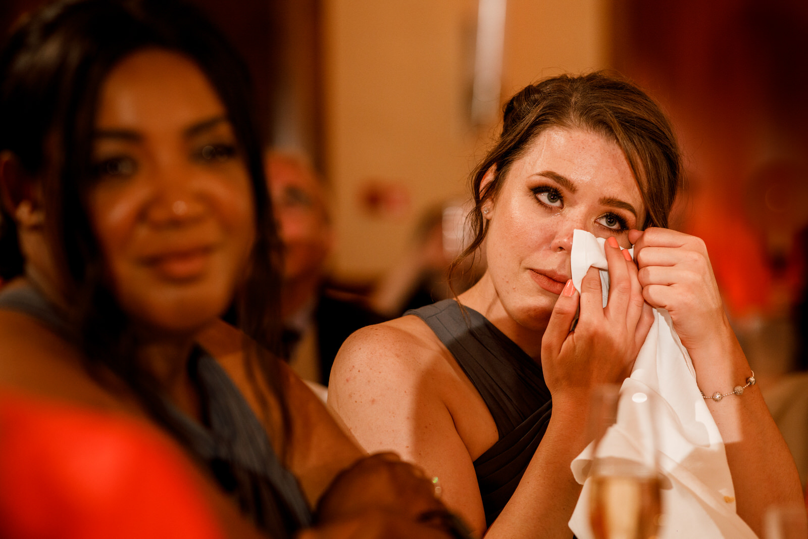 guest wiping eye at wedding speech