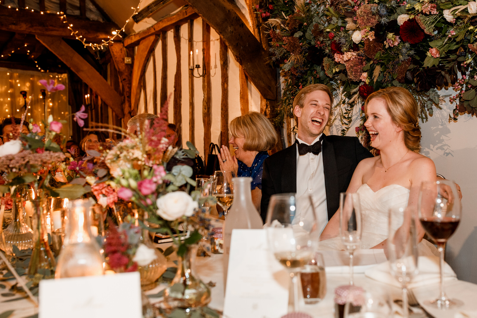 bride and groom laughing at speches at old luxters barn