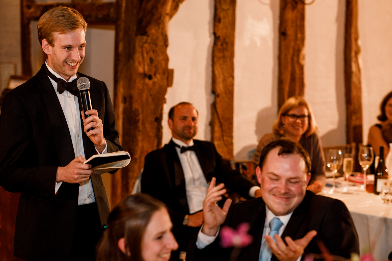 groom laughing at speches at old luxters barn