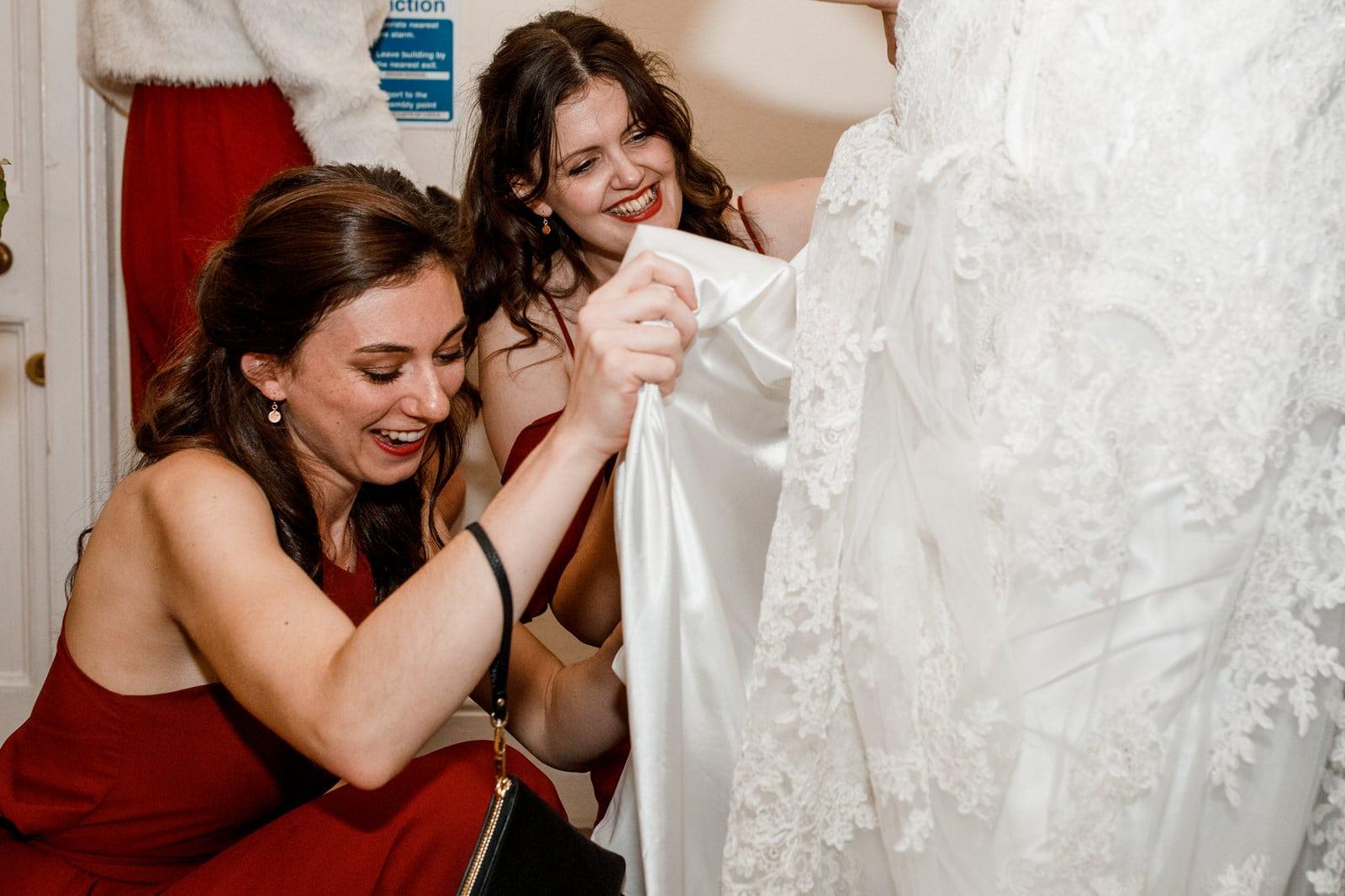 bridesmaid looking up brides dress and laughing