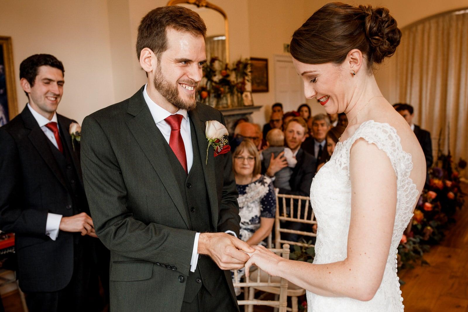 groom placing ring on brides finger at pembroke lodge wedding day