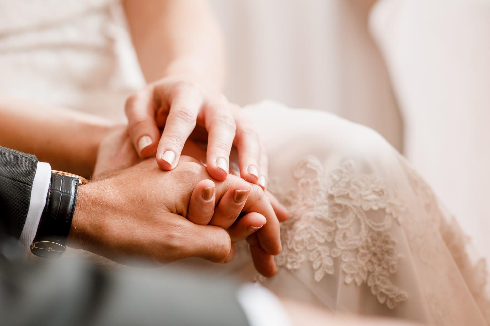 bride and grooms hands interlocked