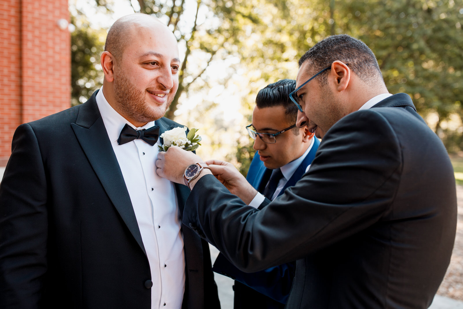 groom having flower pinned to lapel