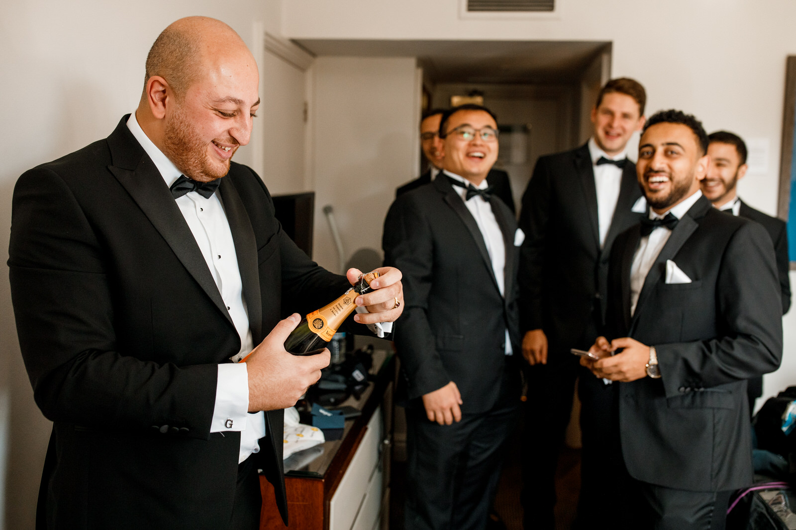 groom opening champagne with ushers