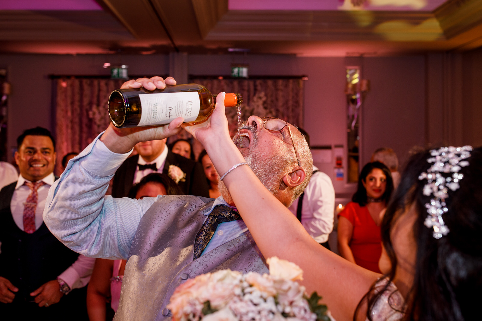 father of the bride swigging wine from bottle