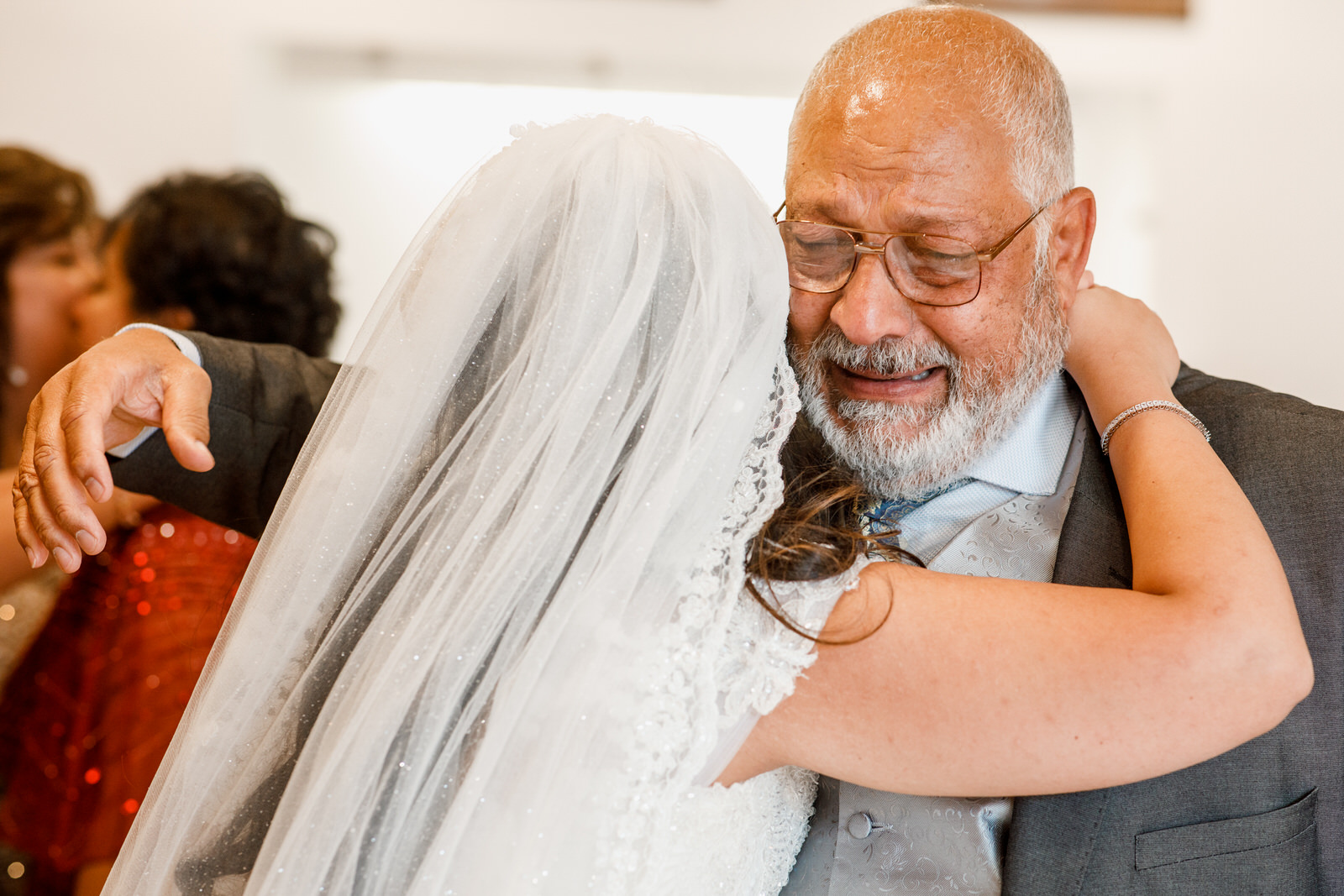father embracing bride and crying