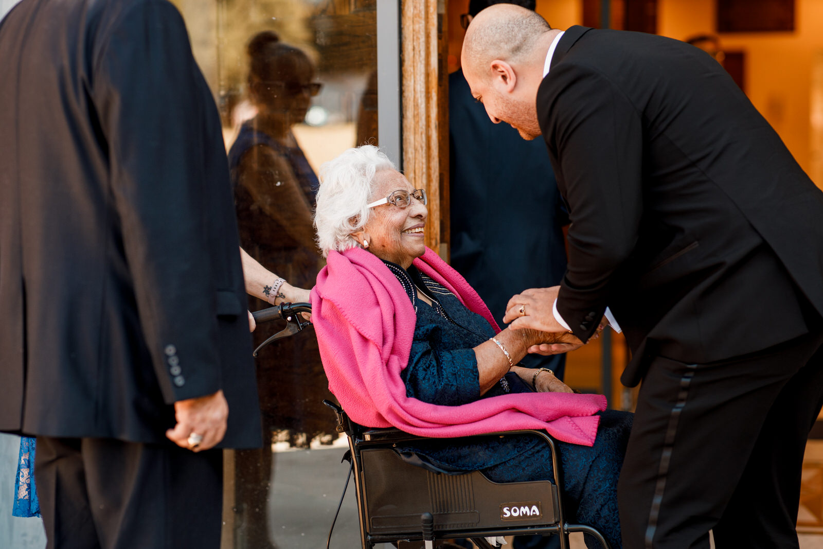 groom greeting grandmother at wedding