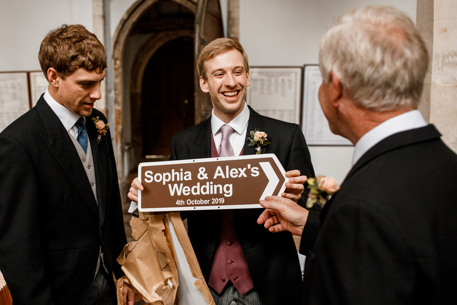 groom holding wedding sign