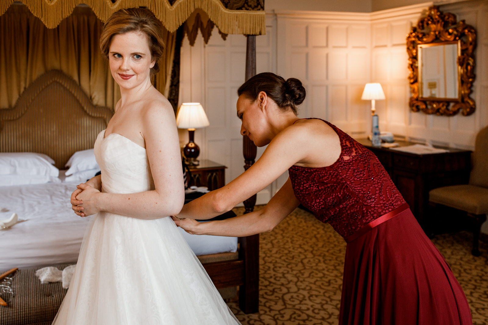 bridesmaid helping bride into her dress