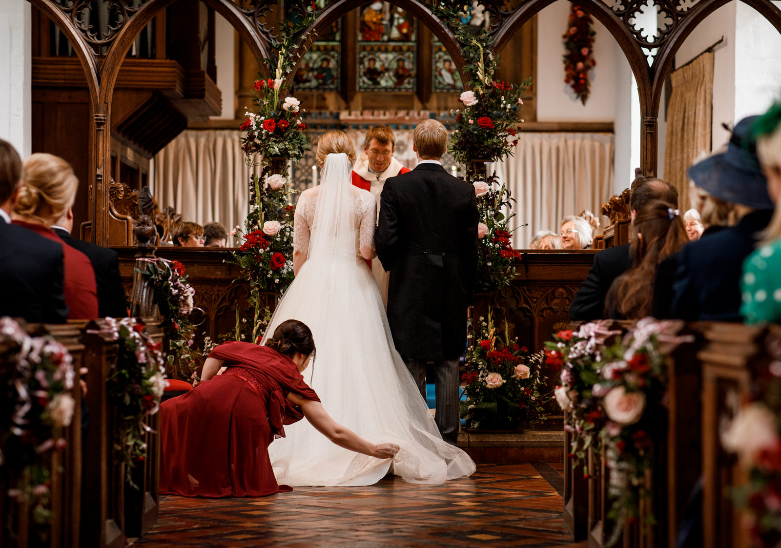 bridesmaid arranging brides dress in church aisle