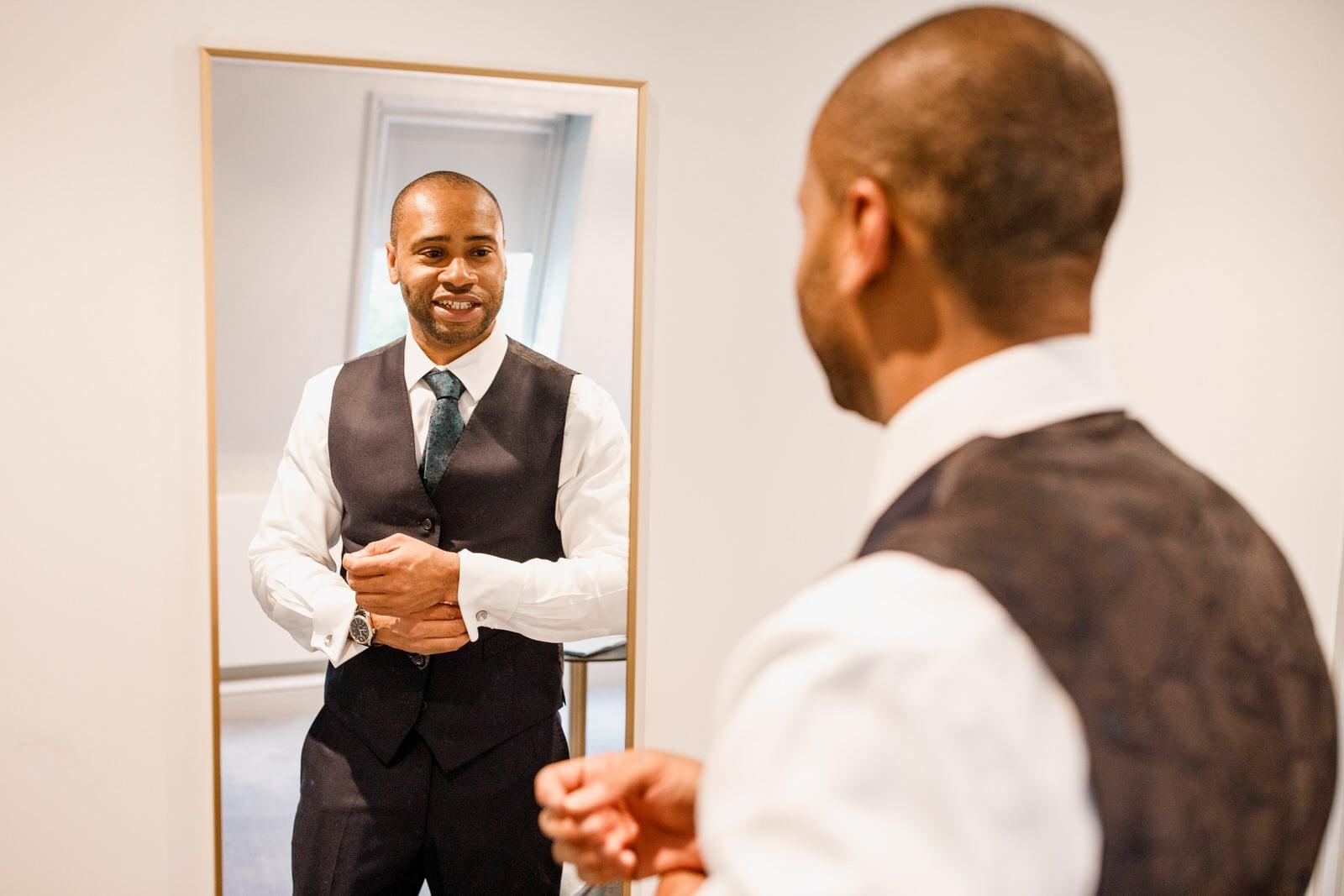 groom putting on cufflinks at burnham beeches hotel