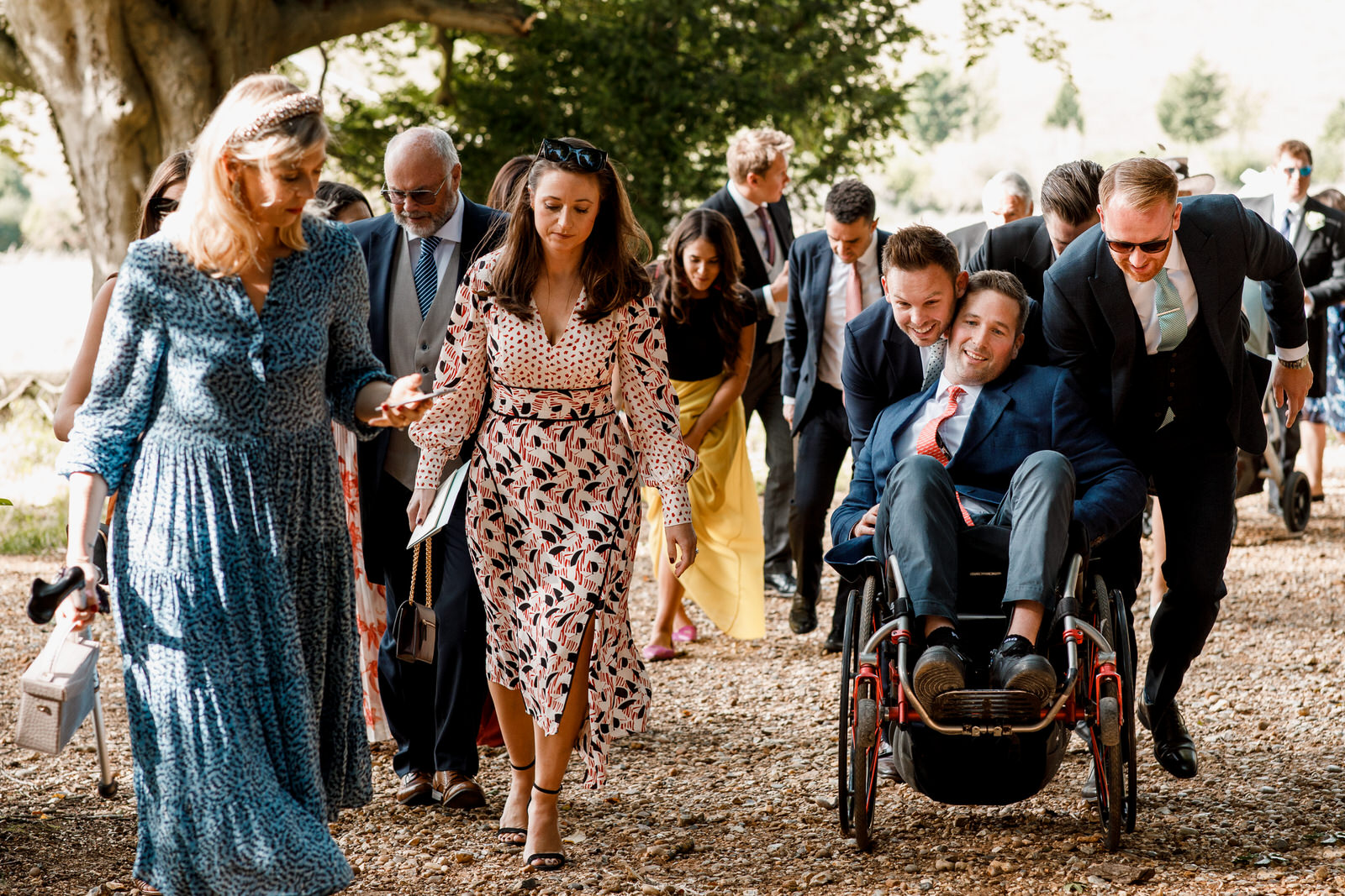 wedding guest pushing wheelchair up hill