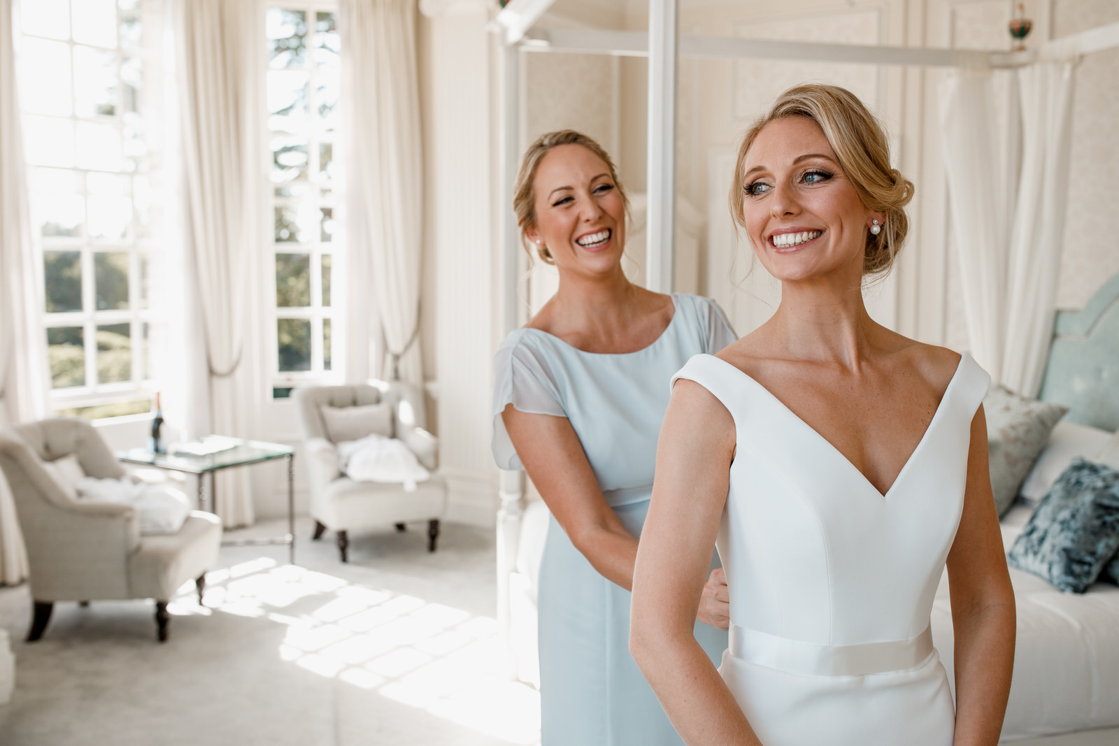 bridesmaid helping bride into dress at hedsor house wedding