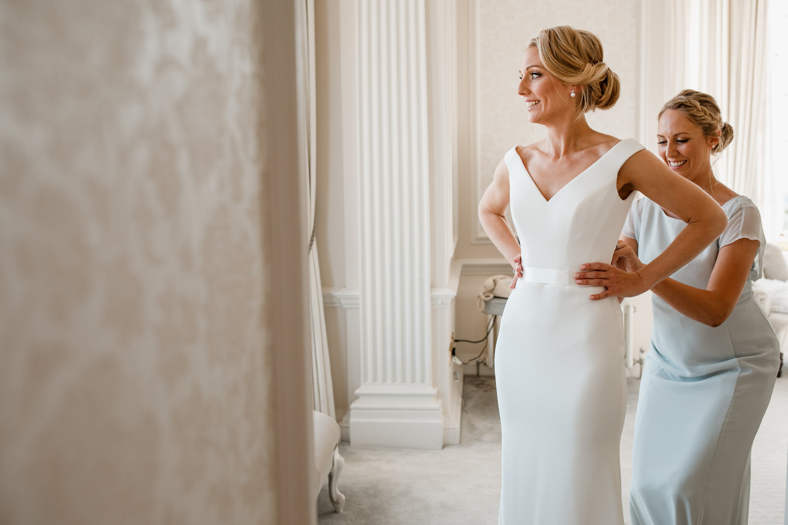bride putting on dress with help from bridesmaid