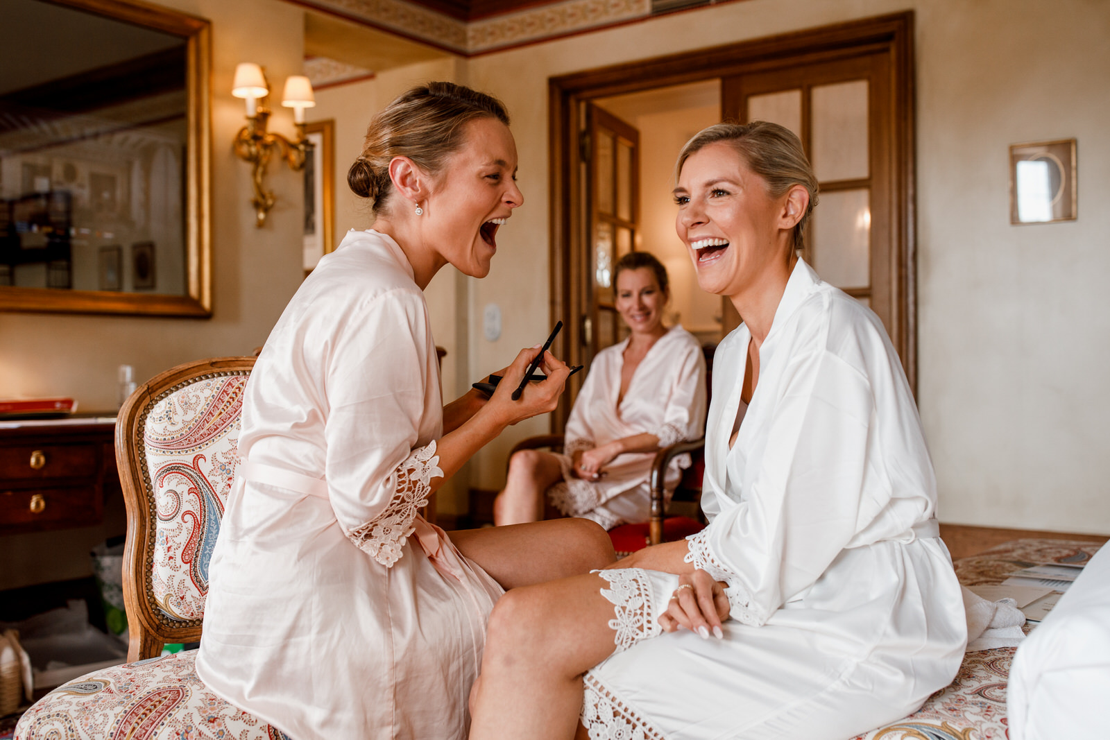 bride and sister laughing as getting ready for french wedding