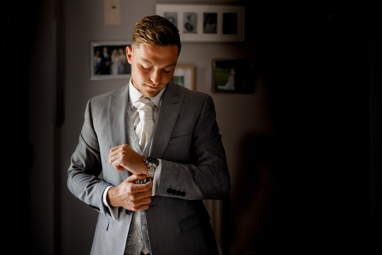 groom getting ready in window light