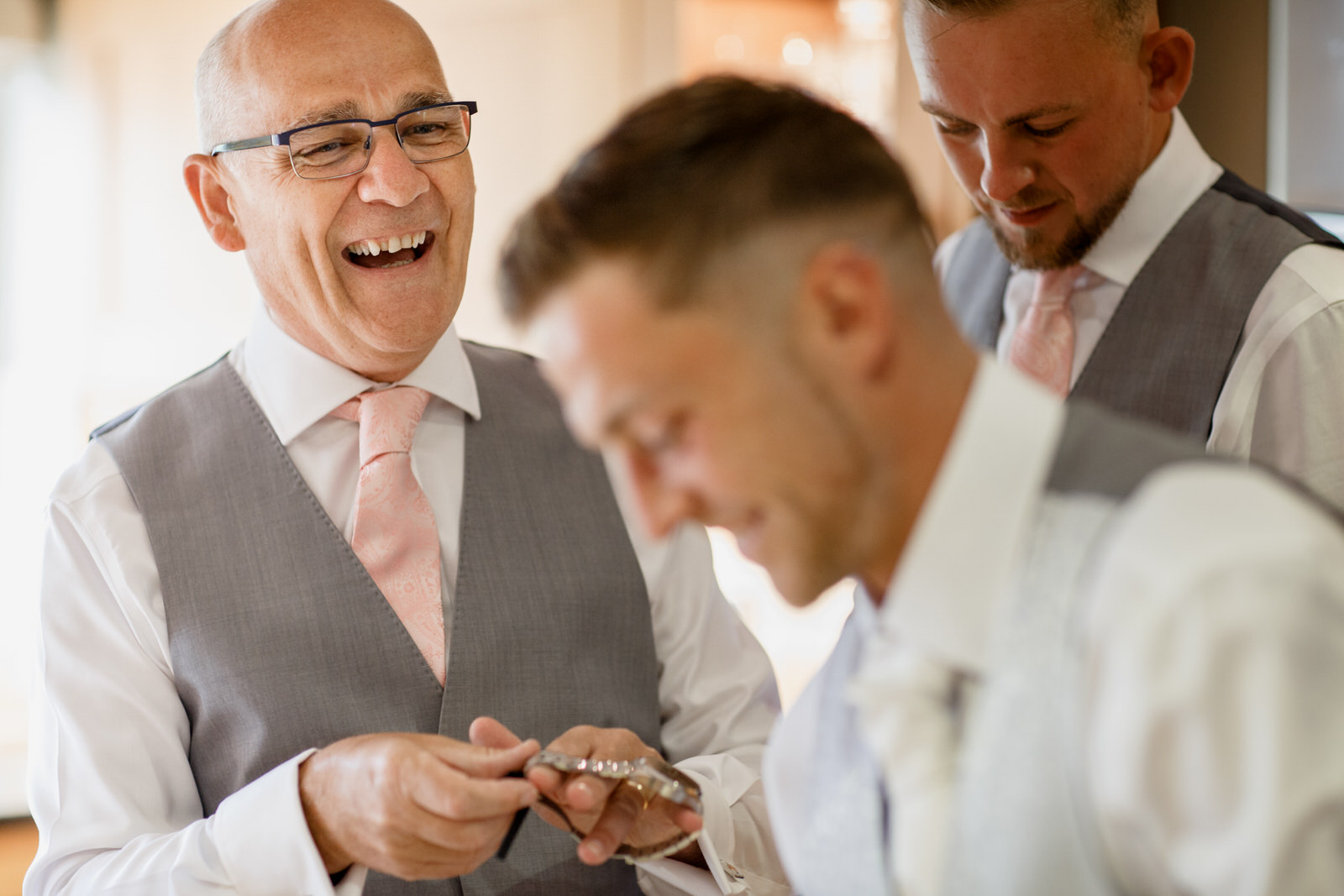 father of the groom laughing with groom