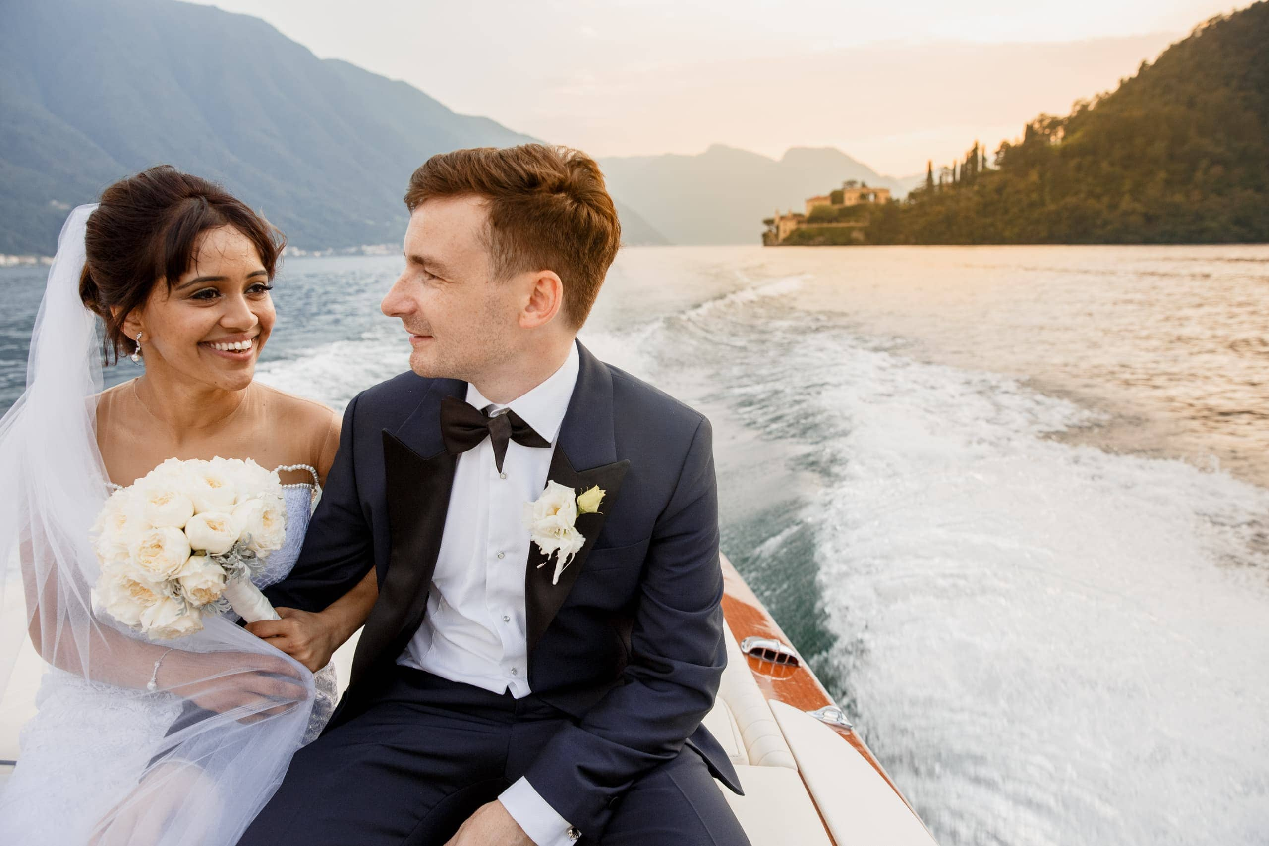 bride and groom on lake como near villa del balbianello