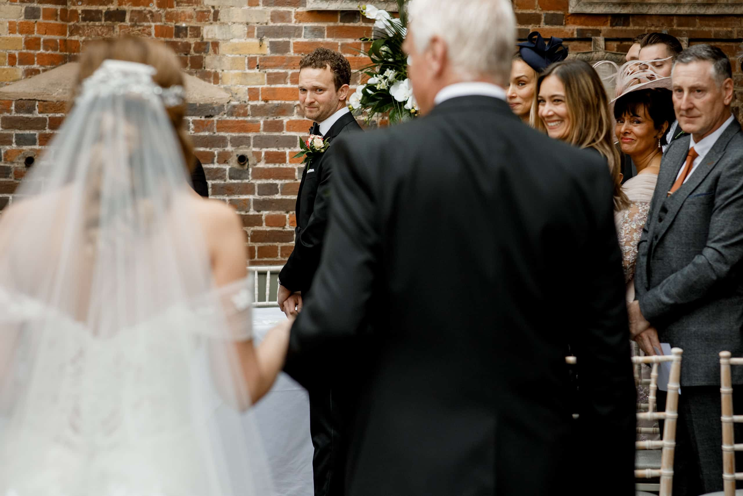 bride walking down aisle with groom looking over shoulder at offley place