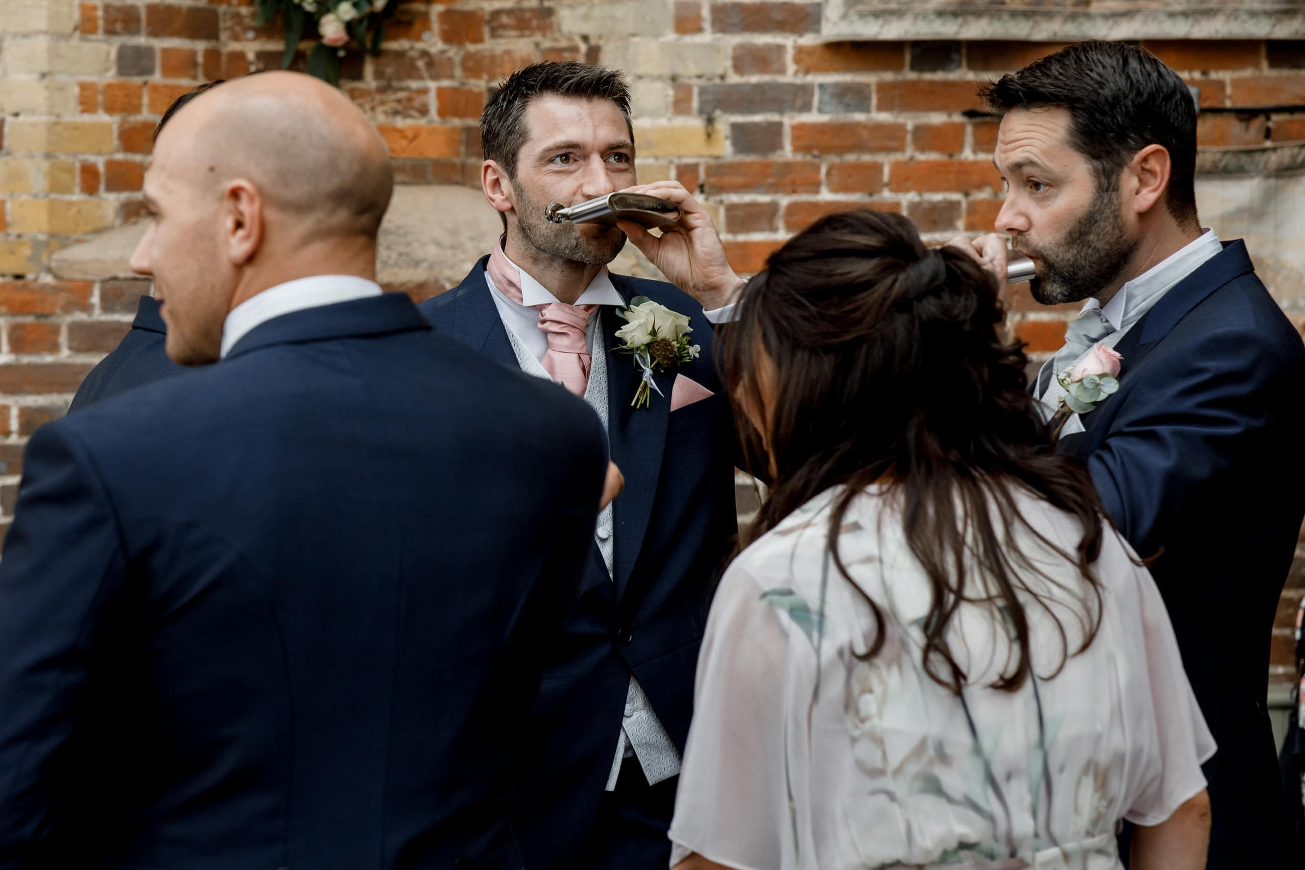 groom taking a drink from hip flask