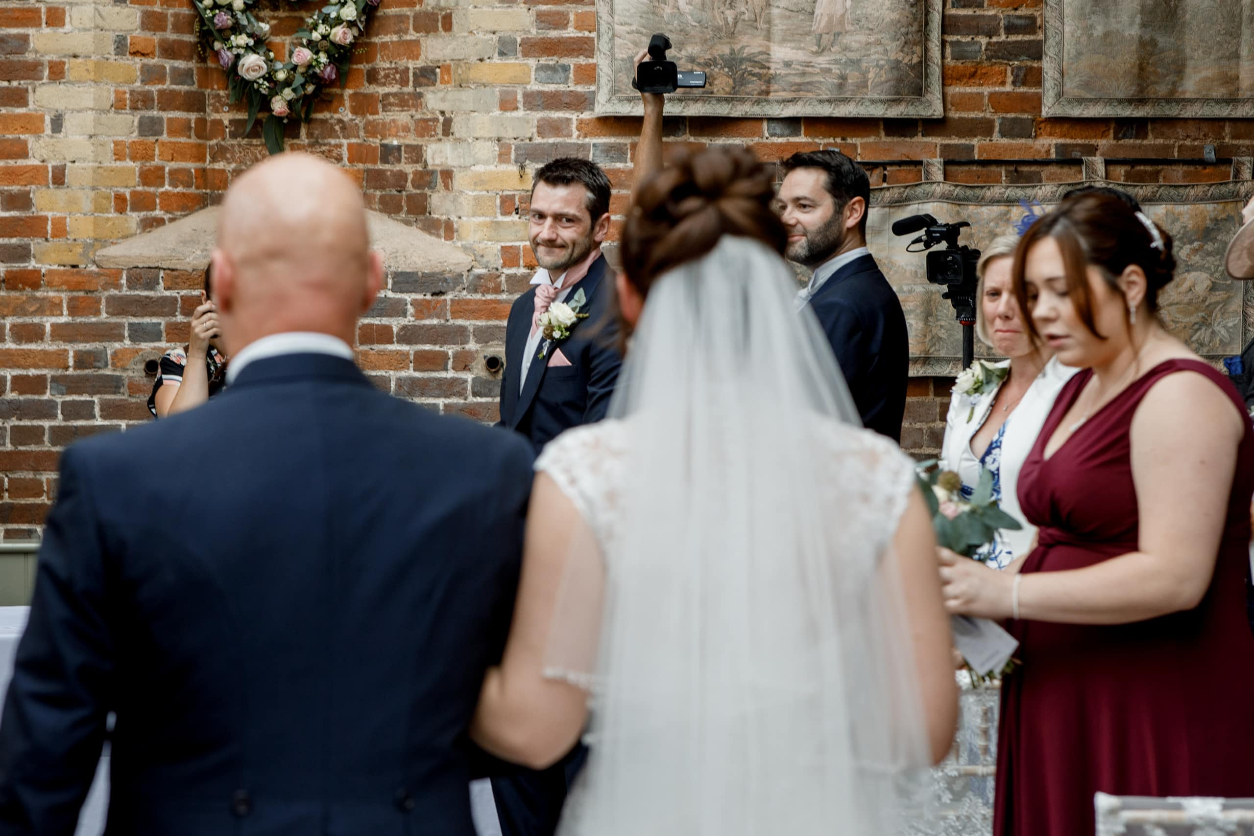 groom looking over shoulder at bride coming down aisle